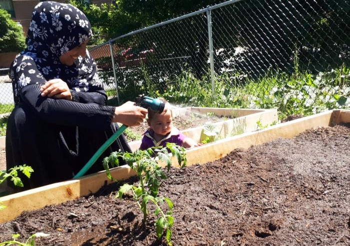 A community member waters plants with her infant