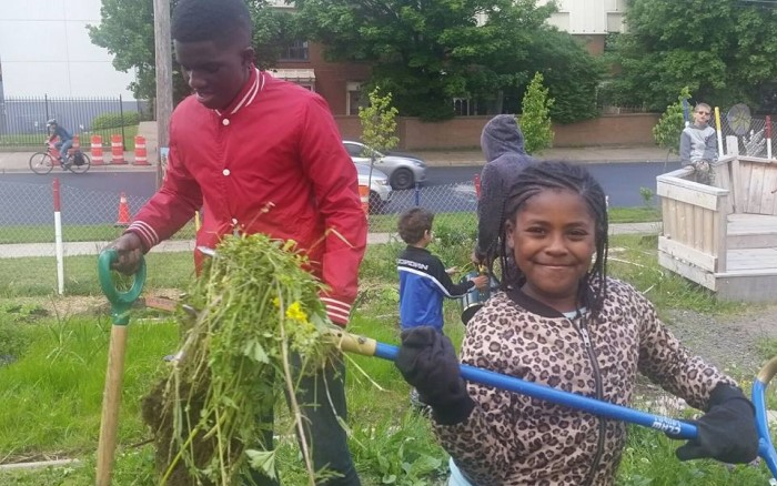 2 youth from Hope Blooms work in the garden